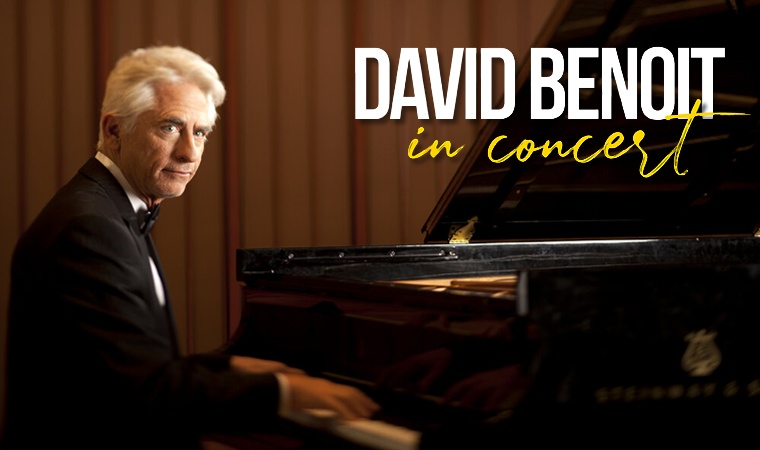 David Benoit seated at a grand piano.