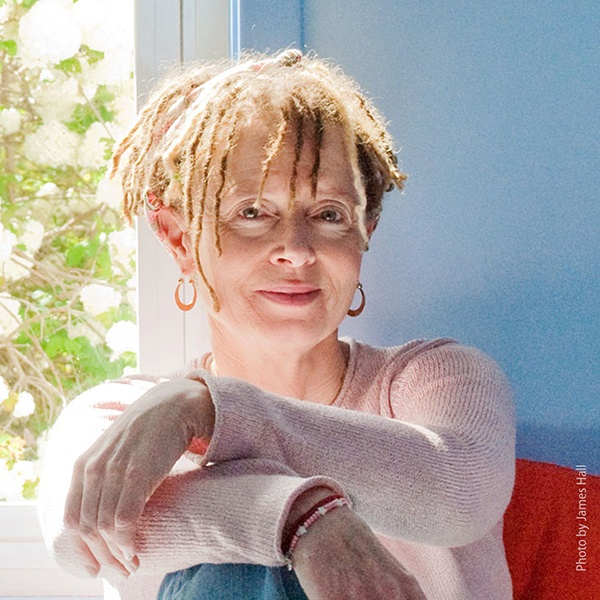 Anne Lamott sitting on a red chair in a light knit sweater, arms cross on her knee. The wall is blue behind her with a window full of a bush in bloom.