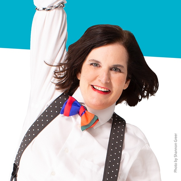 Paula Poundstone smiling with one arm raised wearing white-dotted suspenders and a colorful bow tie.