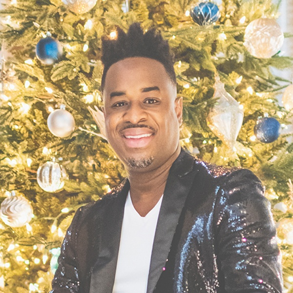 Damien Sneed in a sparkling dark jacket in front of a brightly decorated Christmas tree.