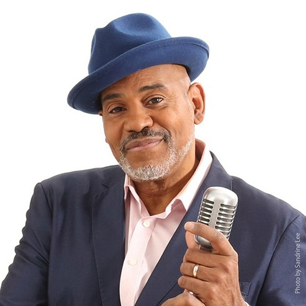 Allan Harris in a blue hat and suit, holding a microphone and smiling to the camera.