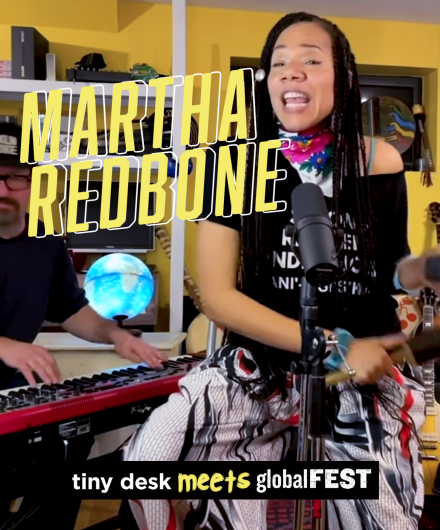 Martha Redbone singing from her home studio. Behind her sits her keyboardist and guitarist, the walls a warm yellow and an illuminated globe in the background.