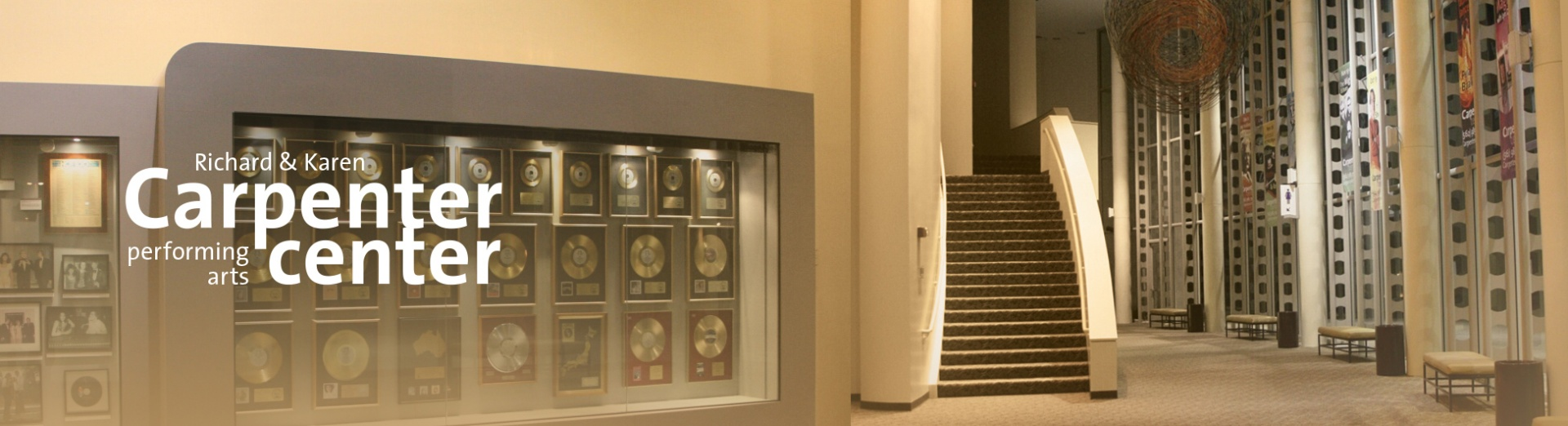 The interior of the Carpenter Center lobby with a case of gold records by the Carpenters visible along one wall.