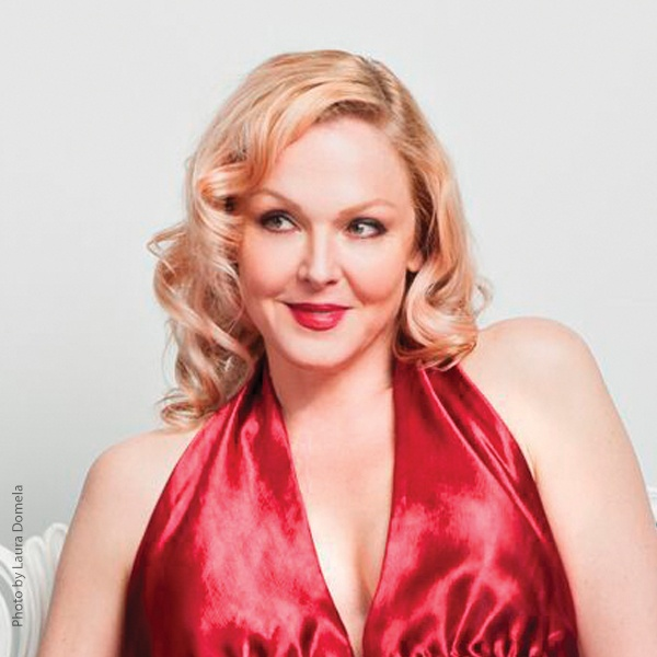 Storm Large in a red dress sitting on a chair and smiling.