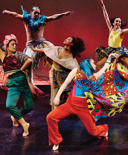 Members of CONTRA-TIEMPO in dance poses wearing vibrant colored clothing.