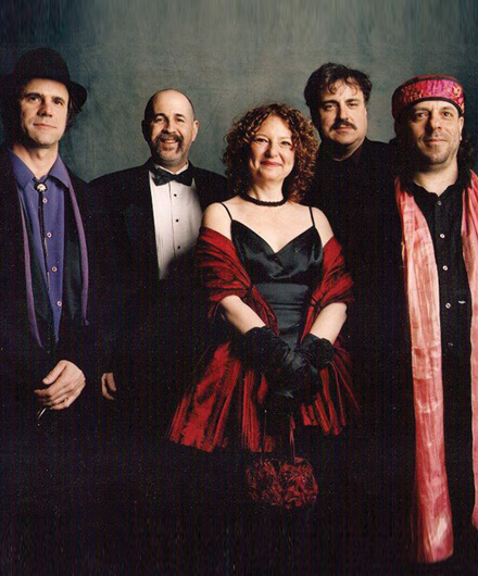 Members of The Klezmatics posing together and smiling.