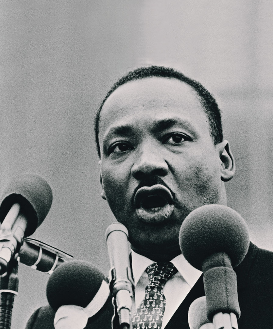 Black and white photograph of Dr. Martin Luther King, Jr. speaking into an array of microphones.