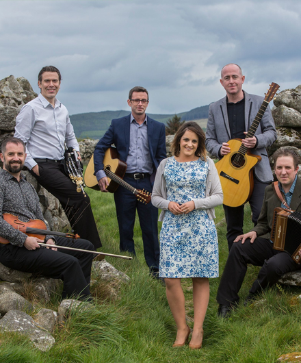 Members of Danú posing with their instruments in the Irish countryside in the opening of an old stone wall, lush green grass at their feet.