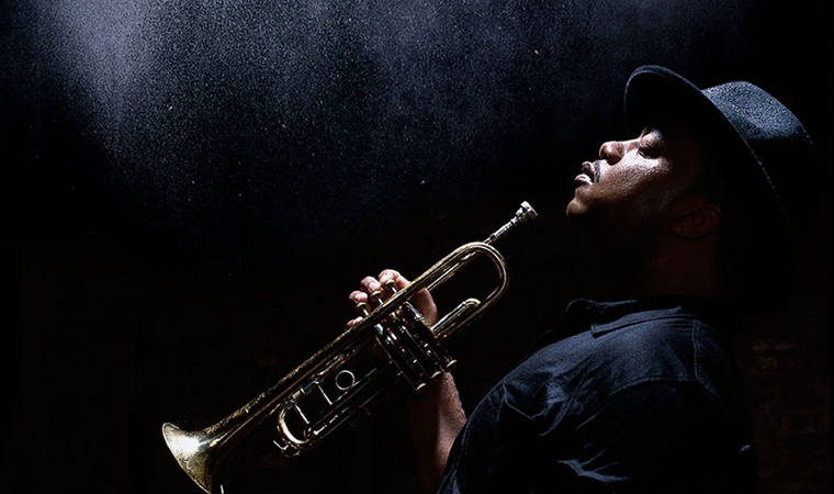Nicholas Payton in profile, holding his trumpet.