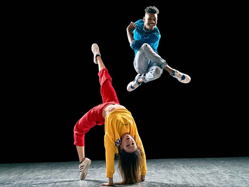 Two dancers from Versa-Style Dance Company on a stage, one jumping high in the air