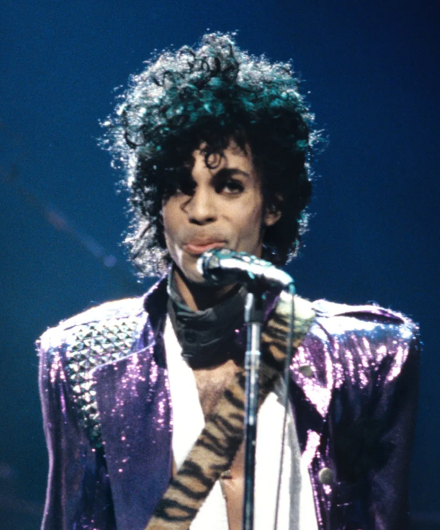 Prince on stage in his signature purple jacket.